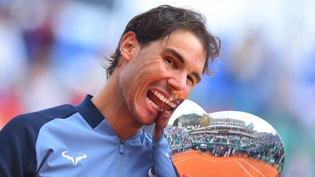 Rafael Nadal beisst in einen Pokal.
