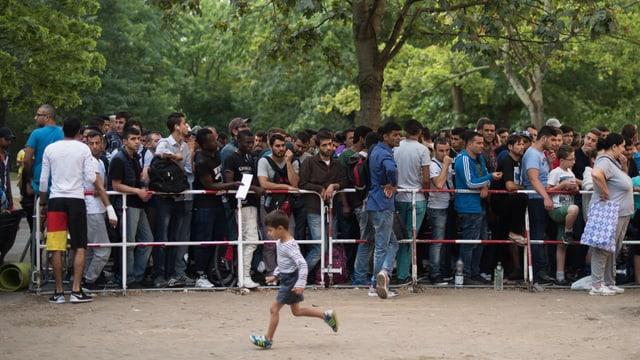 Flüchtlinge warten in einer Schlange vor einem Empfangszentrum in Berlin