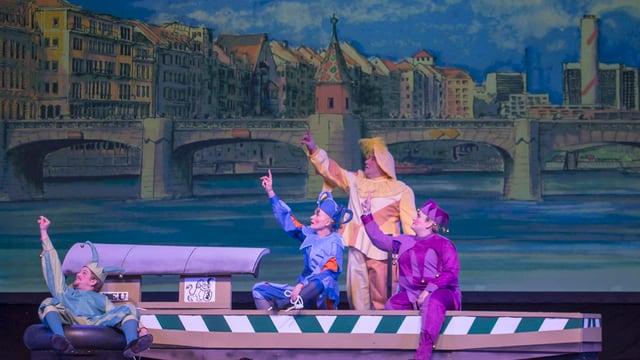 Bühnen-Halbtotale mit Rheinfähre vor Mittlerer Brücke, darin vier Fasnachtsfiguren, den Blick zur Seite gerichtet.