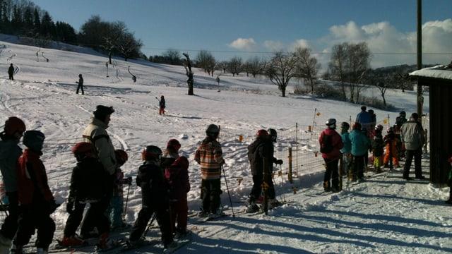 Kinder und erwachsene Skifahrer stehen Schlange am Skilift in Wegenstetten