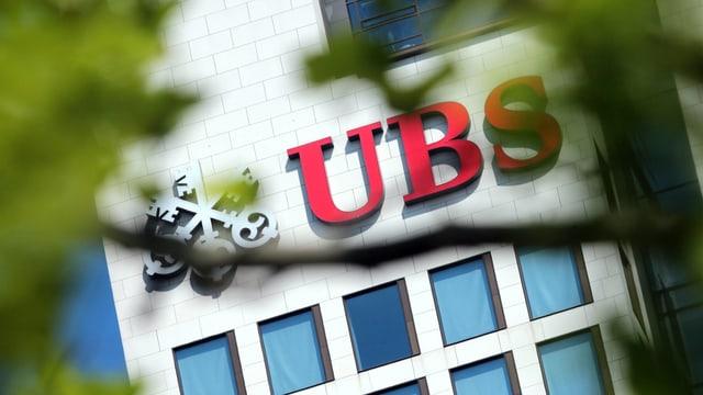 Symbolbild: UBS-Schriftzug an einem Gebäude, fotografiert durch einen Baum hindurch.