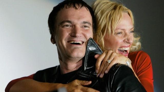 Quentin Tarantino wird von hinten von Uma Thurman umarmt. Beide strahlen dabei um die Wette.