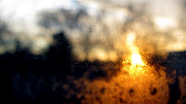 Im Hintergrund eine verschwommene Landschaft bei Sonnenuntergang, im Vordergrund eine Flamme.