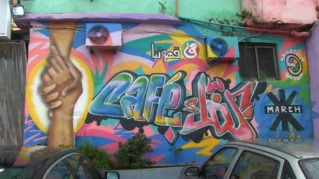 Ein Graffiti an der Wand. Es zeigt zwei Hände, die sich umschlingen.