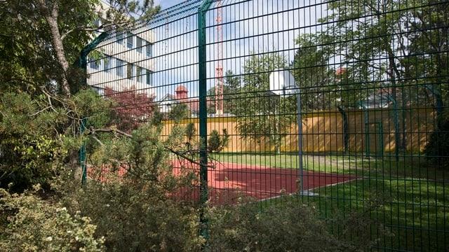 Ein hoher Zaun, dahinter sichtbar ein Sportplatz und die UPK.