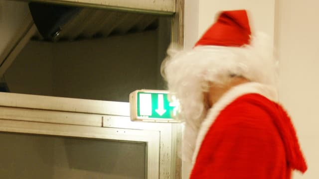 Ein Weihnachtsmann, aufgenommen von hinten, geht Richtung Notausgang.