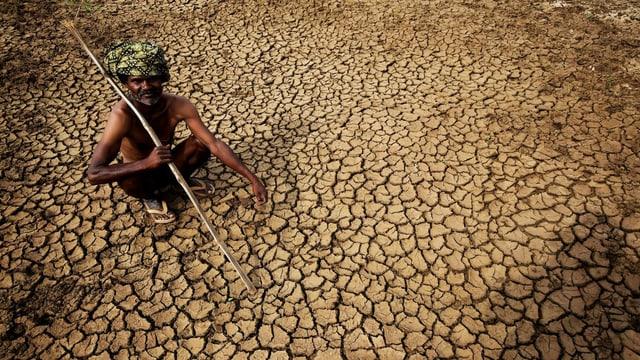 Ein Bauer sitzt auf seinem ausgetrockneten Land