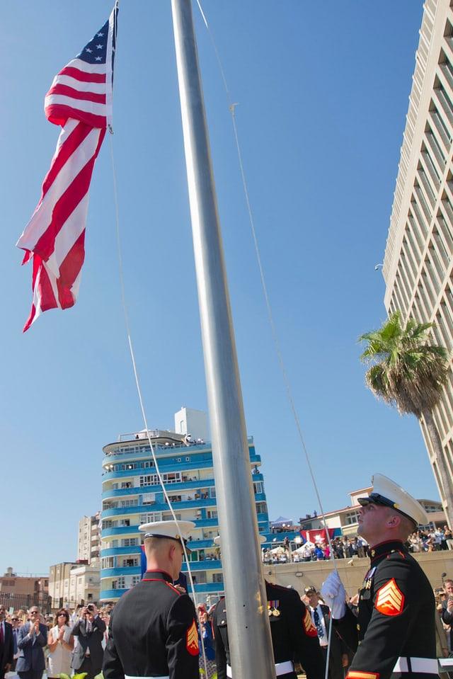 U.S. Marines in Galauniform hissen die US-Fahne vor der Botschaft.