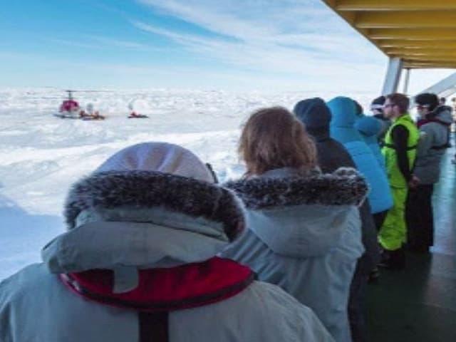 Passagiere schauen auf den auf dem Eis gelandeten Helikopter.