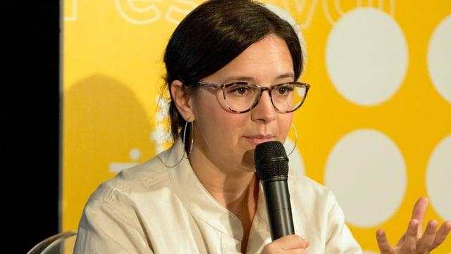 Bari Weiss (mit Brille) spricht in ein Mikrofon.