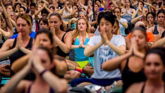 Menschen meditieren in einer grossen Gruppe im Lotussitz.