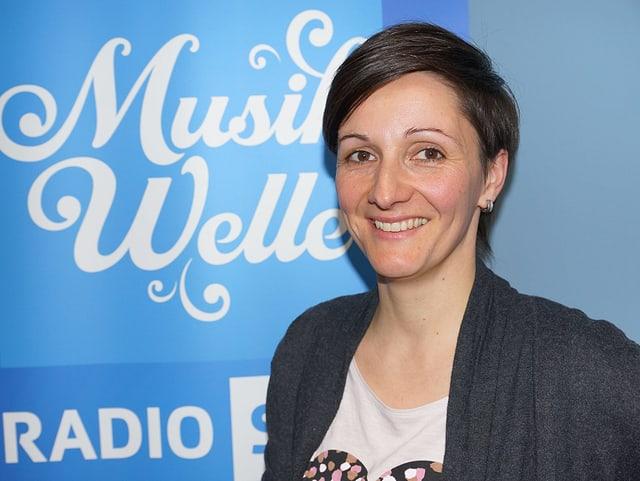 Frau steht vor Musikwelle-Logo.