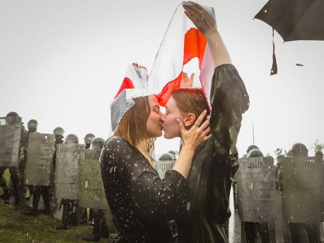 Zwei Frauen küssen sich, hinter ihnen Polizei und Armee mit Schutzschildern.