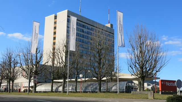 Totale des Bruderholzspitals mit Veloparking und Flaggen im Vordergrund.