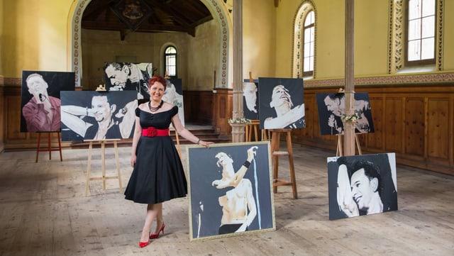Bianca Geronimi im Ausstellungsraum, mit den Bildern des Leadsängers.