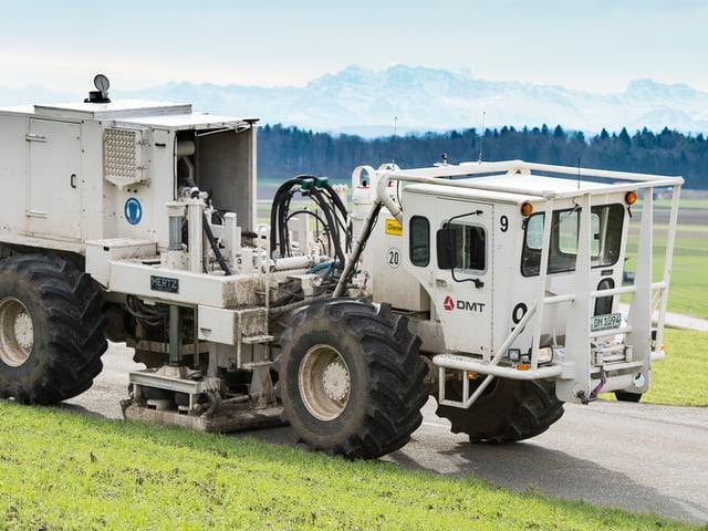 Weisses Fahrzeug mit dicken Pneus und einer unter dem Fahrzeug montierten dicken Stahlplatte, die hydraulisch auf den Strassenbelag gedrückt wird.