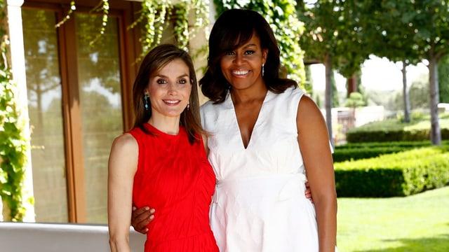 Königin Letizia im roten Kleid posiert neben Michelle Obama, die ein weisses Kleid trägt.