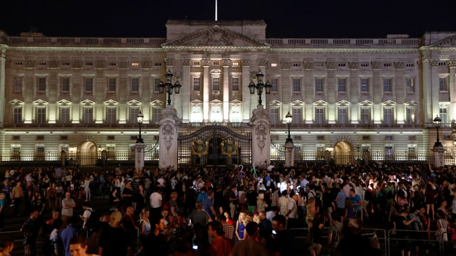Beleuchteter Buckingham Palace am Abend, davor eine Menschenmasse.