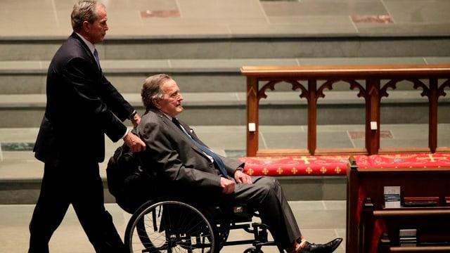 Ein Mann schiebt einen anderen im Rollstuhl (George Bush junior schiebt George Bush senior).