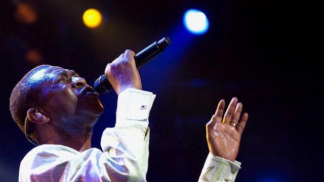 Mann schaut nach oben und singt in ein Mikrofon