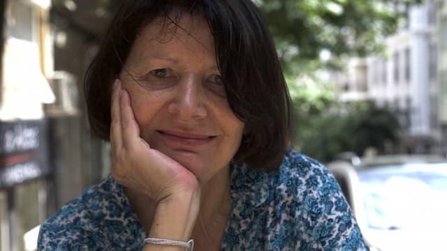 Frau in mittlerem Alter mit dunklen Haaren.