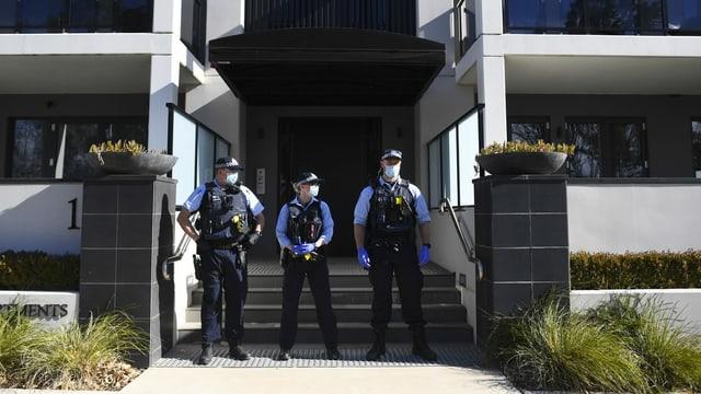 Drei Beamte vor einem Gebäude mit Masken