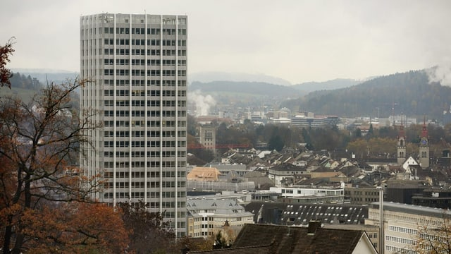Sicht auf Winterthur mit rauchenden Kaminen, Links ein Hochhaus, rechts die zwei Türme der Stadtkirche.