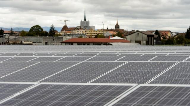 Dach mit Solarzellen-Elementen, im Hintergrund eine Stadt.