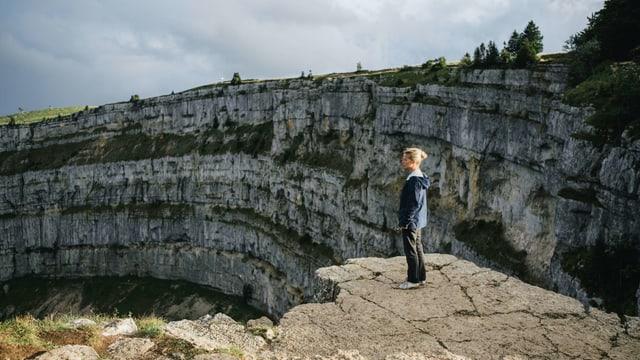 Eine Frau steht am Rand über einer steil abfallenden Felswand