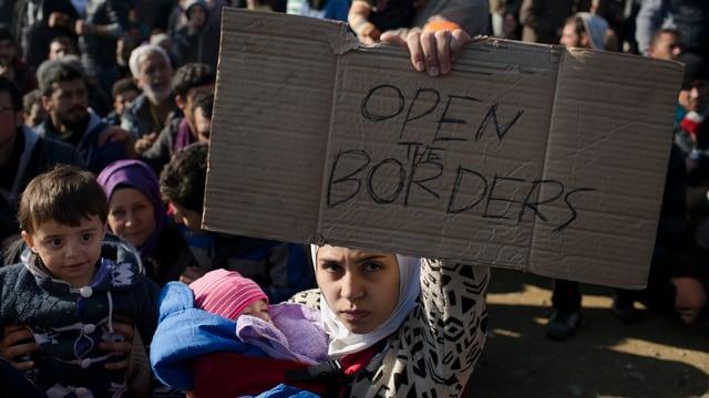 Eine Frau hält ein Schild mit der Aufschrift «Open the Borders»