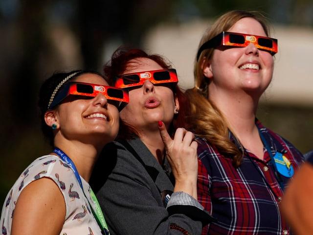 Drei Frauen beobachten die Sonnenfinsternis mit einer Schutzbrille.