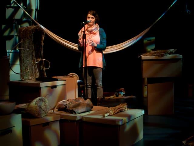 Aninna Polivka inmitten des Bühnenbildes mit Archivschachteln und einer Hängematte