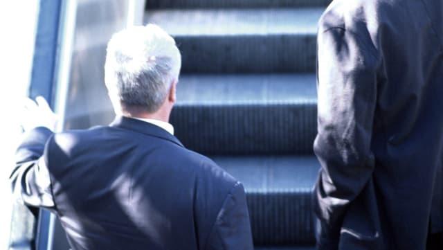 Älterer Mann auf Rolltreppe.