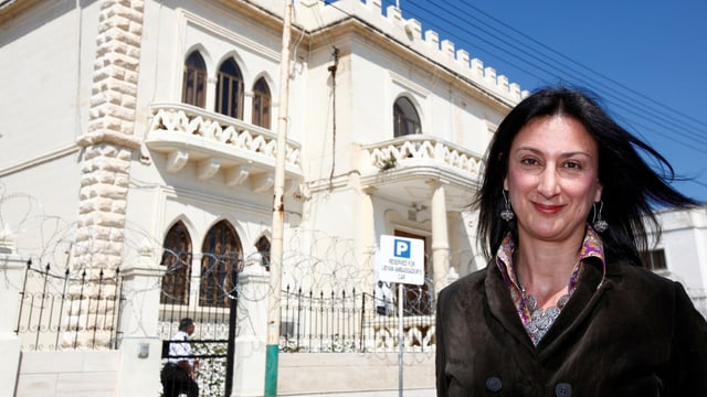 Frau vor einem weissen Gebäude.