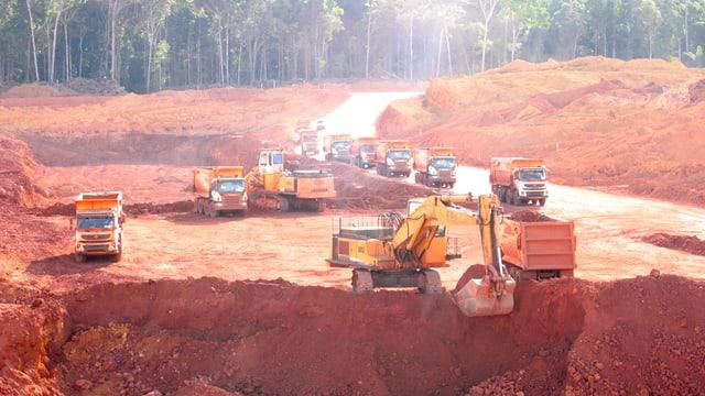 Lastwagen und Bagger beim Abbau von Bauxit-Erz im brasilianischen Regenwald.