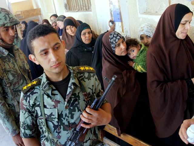 Militär neben Wählerinnen.