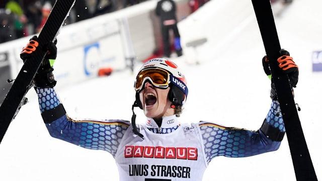 Linus Strasser streckt vor Freude seine Skier in die Luft.