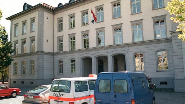 Gebäude aus Stein, davor Polizeiautos.