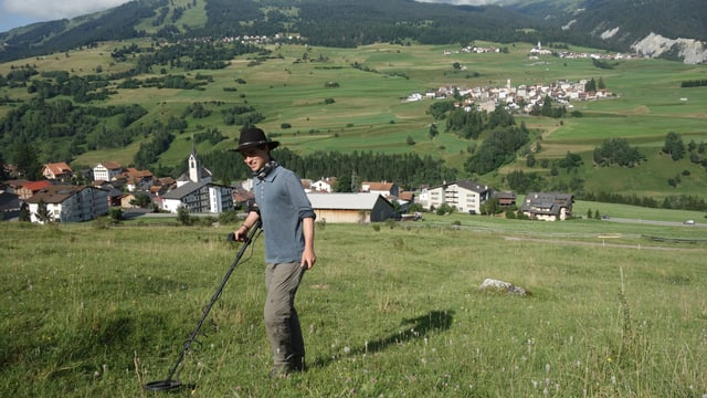 Simon Kurmann, il student da l'Universitad da Turitg examinescha il terren sur Cunter cun in detectur da metal.