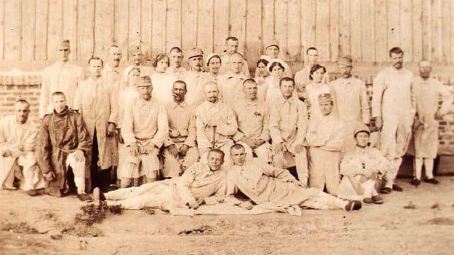 Eine Gruppe von Pflegern und Krankenschwestern vor einem Holzgebäude.