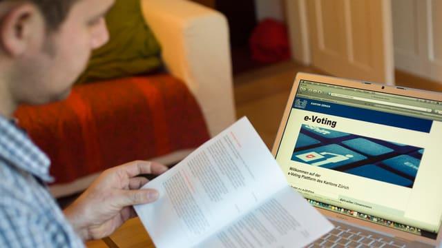 Mann mit Wahlunterlagen vor Computer-Bildschirm.