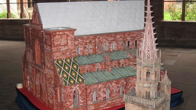 Ein kleines Münster aus rotem Plastik noch ohne Türme, daneben steht ein alter Turm aus Holz.
