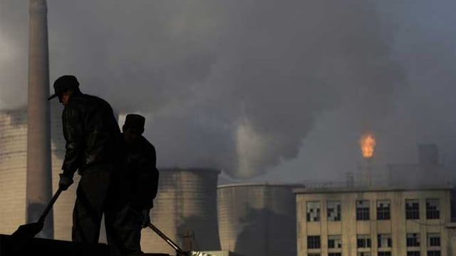 Im Vordergrund Arbeiter, im Hintergrund qualmende Schornsteine in China.