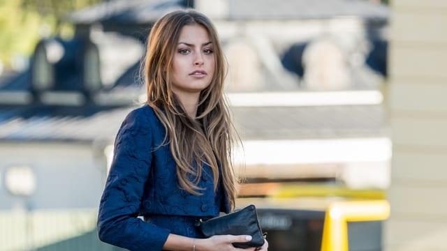 Milena trägt die lange, hellbraunen Haare offen. Gekleidet ist sie in ein royalblaues Deux-Pièces mit passender Clutch.