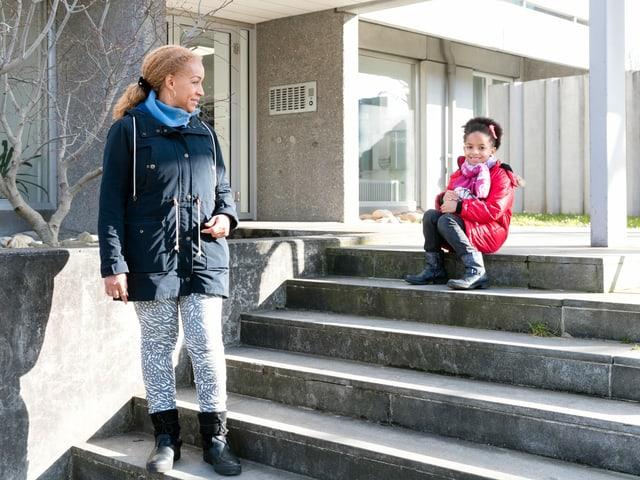 Eine Frau blickt in Richtung ihrer Tochter, die auf einer Treppe sitzt.