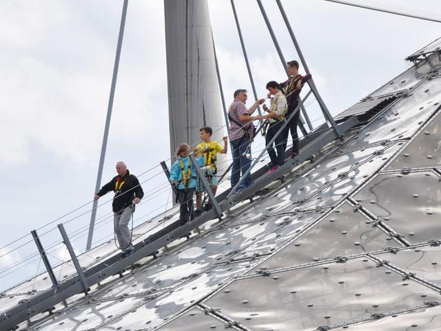 Touristen gehen über das Olympiadach.
