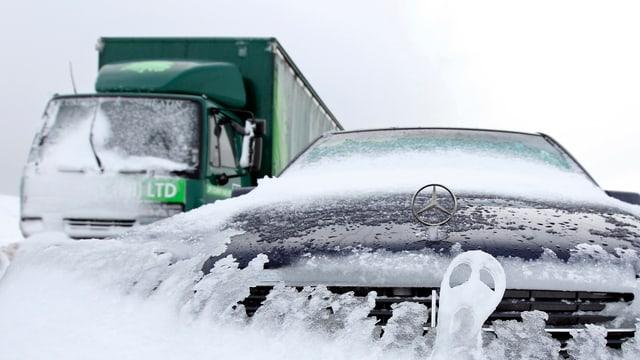 Ein Lastwagen und ein PW von Mercedes mit vereisten Frontscheiben und Kühlergrill-