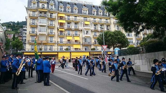 Musicants sin las vias da Montreux, cun vista sin il Palace Hotel da Montreux.
