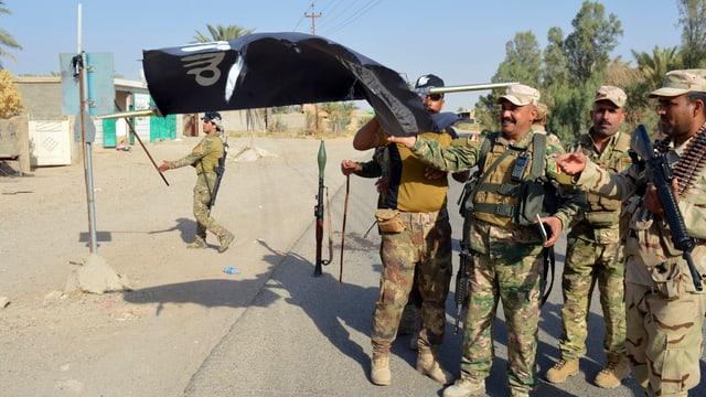 Soldaten der irakischen Armee entfernen eine IS-Flagge.