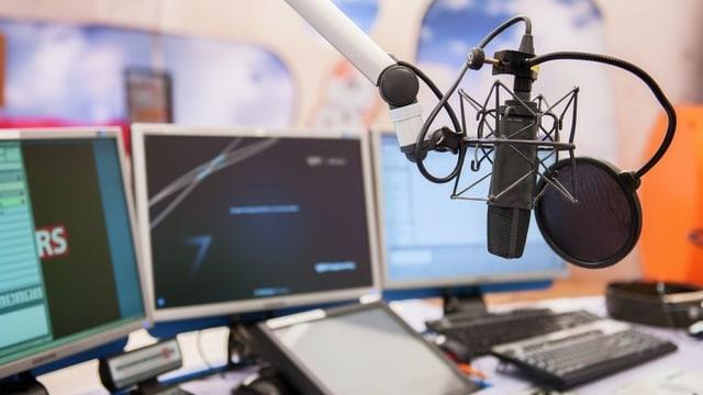 Ein Radiostudio mit einem Mikrofon und drei Bildschirmen